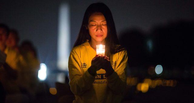 אישה מחזיקה נר ביחד עם עוד מתרגלי פאלון גונג בעצרת נרות שנערכה באנדרטת לינקולן בוושינגטון הבירה, ב-20 ביולי 2017, כדי לכבד את אלה שמתו במהלך הרדיפה שהחלה ב-20 ביולי 1999 על ידי המשטר הקומוניסטי בסין (בנג'מין צ'סטין)