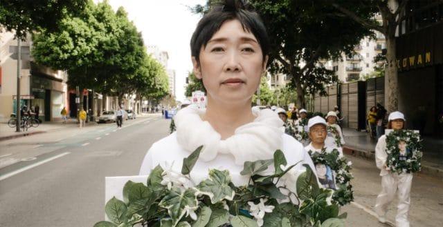 <b>וואנג יי-פיי האבלה </b> מחזיקה 'זר אבל' לכבוד אחותה שנהרגה במחנה עבודה סיני בשל אמונתה בפאלון גונג. גב' וואנג נמלטה מסין כדי לברוח מאותו גורל, והיא נראית כאן בצעדה שנערכה בלוס אנג'לס בשנת 2016.