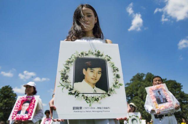 """מפגינים מפאלון גונג אוחזים בתמונות הנצחה בעת צעדה על גבעת הקפיטול בוושינגטון הבירה ב-17 ביולי 2014, כחלק מהאירועים בחסות אגודת הפאלון דאפא בוושינגטון למען סיום """"הרדיפה של המשטר הסיני נגד מתרגלי פאלון גונג"""". צילום: AFP  ג'ים ווטסון"""